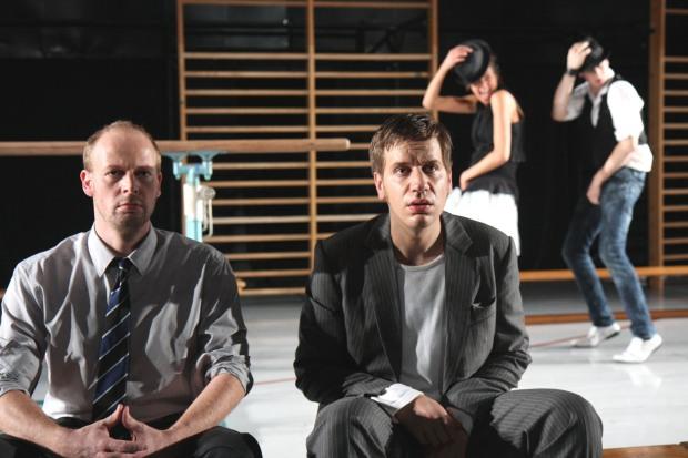Die Schauspieler Gregor Henze als John Fontanelli und Lutz Wessel als Malcolm McCaine sitzen in Anzügen auf der Bühne