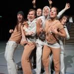 6 Schauspieler in geigefarbener Joggingkleidung bei der Aufführung von Eine Billion Dollar