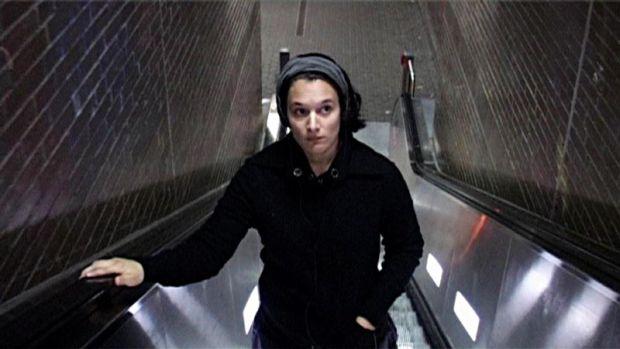 Eine junge Frau mit dunklen Haaren in einem schwarzen Pullover steht auf einer Rolltreppe. Sie ist nach oben fahrend zu sehen, direkt auf die Kamera zu.
