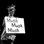 """Eine Frau hebt ein Plakat hoch, auf dem """"Musik, Musik, Musik"""" steht"""