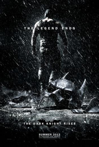 Plakat zu The Dark Knight Rises Der muskulöse Bane wendet dem Betrachter seinen Rücken zu und verschwindet im Dunkel des Hintergrundes. Im Vordergrund liegt Batmans zerschmetterte Maske im Regen. Der Schriftzug The Legend ends ist zu lesen.