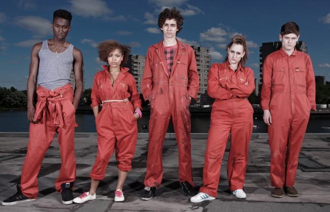 Fünf Jugendliche in orangefarbenen Overalls stehen an einem urbanen Seeufer. Alle schauen in Richtung der Kamera. Ganz links steht ein sportlicher Schwarzer, der das Overall-Oberteil heruntergekrempelt hat und ein graues armloses Shirt trägt. Rechts von ihm steht eine Schwarze, die trotz des Overalls dank Accessoires wie Gürtel, Armreifen und Schuhen einen eleganten Eindruck macht. Sie verschränkt ihre Arme.Rechts von ihr, in der Mitte, steht lässig ein Weißer mit schwarzen lockigen Haaren und den Händen in den Hosentaschen. Rechts von ihm eine Weiße mit stark zurückgebundenen Haaren und verschränkten Armen. Ganz rechts steht ein Weißer mit leicht gesenktem Blick und in die Stirn gekämmten Haaren. Alle machen eher einen abweisenden Eindruck.