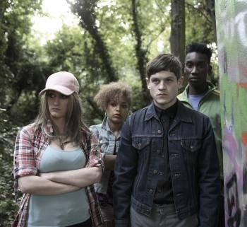 Vier Jugendliche stehen in einem bewaldeten Gebiet. Rechts von ihnen ist eine mit Grafitti übersähte Betonwand zu sehen.