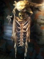 Ein Axolotl aus Stoff in braunem und khakifarbenem Tarnmuster. Unter ihm ein gelber Schädel und ein skelettierter Brustkorb in Tarnfleck.