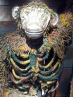 Schimpanse aus Militäruniformen und Metall gefertigt. Das Gesicht ist blank, der Rumpf besteht aus den Rippenknochen in gün und olivgrün.