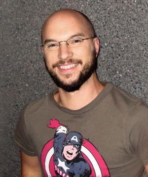 Martin Wolkner, Gründer und Hauptveranstalter der Homochrom Filmreihe - ein junger Mann mit Brille, kurzem Vollbart, glattgeschorenem Kopf und Captain-America-Shirt