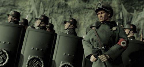 Mehrere Puppen in Nazi-Uniformen, im Vordergrund eine Puppe in grauem Wehrmachtsmantel mit Stahlhelm, im Hintergrund mehrere Soldaten, die schwarze mannshohe Schilde tragen.