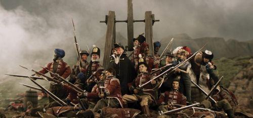 Mehrere Puppen im Pulverdampf. In der Mitte Winston Churchill mit typischer Zigarre, umgeben von Soldaten in Uniformen des 18. Jahrhunderts, den klassischen Rotröcken.