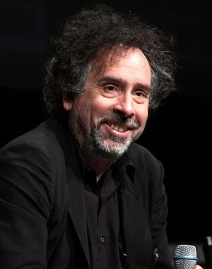 Der Regisseur Tim Burton: Ein Mann in den Fünfzigern mit grauen Bartstoppeln und etwas wirren schwatzen Haaren mit einzelnen grauen Strähnen. Er lächelt etwas schief und trägt ein schwarzes Hemd sowie ein schwarzes Sakko.