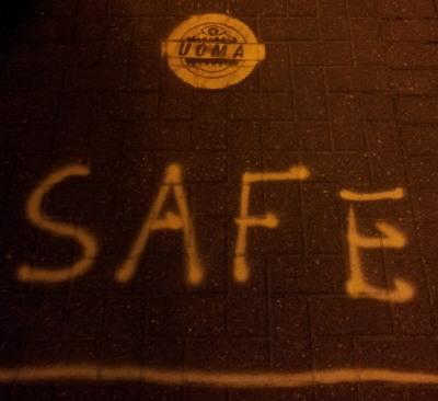Mit gelber Sprühfarbe ist das Logo der UOMA, das Wort Safe und eine gelbe Linie auf das Pflaster gesprüht