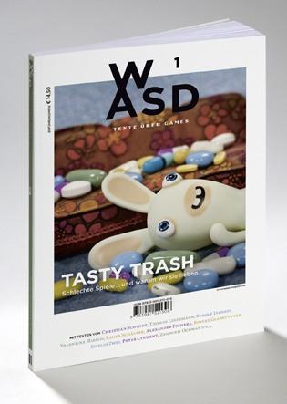 Das WASD-Magazin. Ein aufrechtstehendes Buch, auf dem Cover liegt eines der Crazy Rabbits aus dem gleichnamigen Spiel zwischen Pillen und Tabletten vor einer Couch. Unten steht der Titel Tasty Trash schlechte Spiele und warum wir sie lieben.
