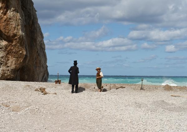 Ein Strand im Sonnenschein. Ein Mann mit Strohhut steht in einer Grube, neben ihm ein Mann in Frack und Zylinder