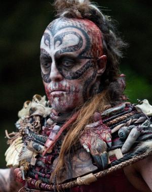 Ein Kona-Krieger mit Gesichtsbemalung: 2 Schlangen winden sich um seine Augen und treffen auf der Stirn zusammen. Um den Mund ist seine Bemalung blutrot, um den Hals hängen Finger, Augen, Haarschöpfe und Schmuck.