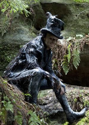 Old Georgie trägt schwarz: Stiefel, Frack und Zylinder. Er sitzt auf ein paar Steinen im Wald und grinst teuflisch