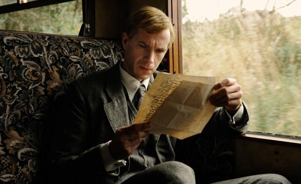 Ein junger blonder Mann in einem grauen Anzug sitzt in einem altmodischen Zugabteil. Er schaut konzentriert auf einen Brief, den er mit beiden Händen hält.
