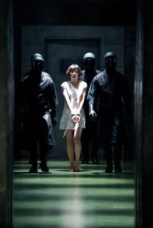 Eine junge Frau in einem weißen Kleid wird von drei Gestalten in schwarzen Uniformen mit gesichtsverhüllenden Helmen eskortiert. Sie hat nackte Füße und ihre Hände sind mit Handschellen gefesselt.
