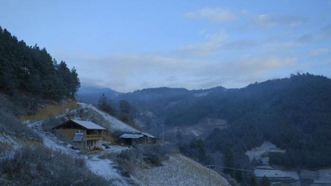 Bläulich schimmernde Berge mit beschneiten Wäldern. Im linken Drittel steht ein Holzhaus.