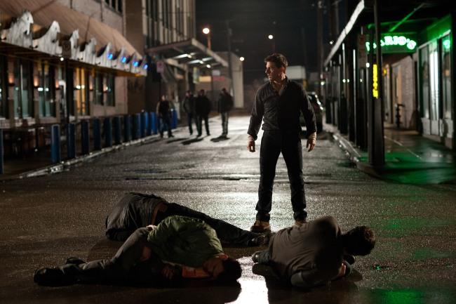 Tom Cruise steht in Jeans und Hemd über drei zusammengekrümmten Männern auf einer regennassen Straße