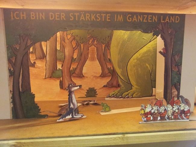 Ein Märchenwald aus Papier: Der Wolf, die sieben Zwerge, ein Frosch und die Beine von einem Riesensaurier, die nicht ins Bild passen.