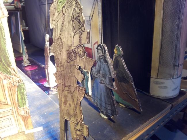 Zwei Papierfiguren in der Gestalt viktorianischer Frauen hinter der Bühne