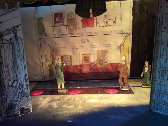 Drei Papierfiguren viktorianischer Gentlemen im Bühnenbild aus Papier