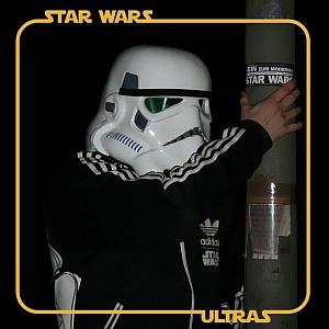 """Ein Mann mit Stormtrooper-Helm klebt einen Aufkleber """"Gegen das moderne Star Wars"""" an einen Laternenpfahl"""