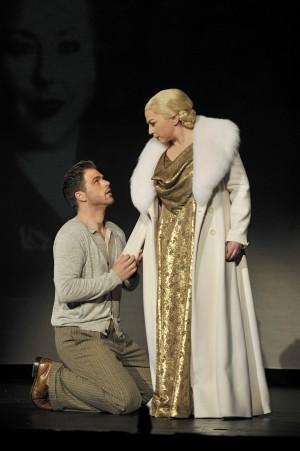 Ein Mann kniet vor einer blonden Frau in Pelzmantel und goldener Robe. Patrick Stanke als Che Guevara und Banu Böke als Eva Perón.
