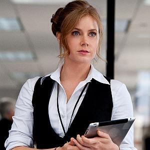 Amy Adams als Lois Lane. Eine rothaarige Frau, die Hemd und Weste trägt. In der Hand ein Pad.