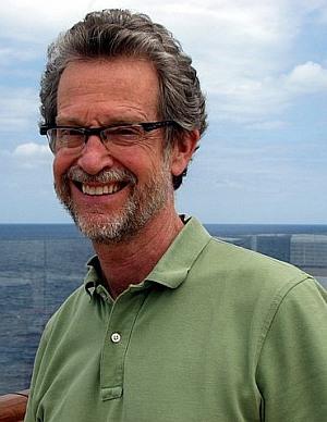 Ridley Pearson - ein älterer bärtiger Mann blinzelt grinsend ins Sonnenlicht, hinter ihm das Meer