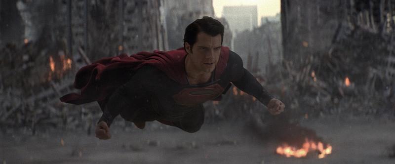 HENRY CAVILL als Superman MAN OF STEEL. Ein Mann mit schwarzen Haaren, blauem Anzug und fotem Umhang fliegt durch eine rauchende, brennende Trümmerlandschaft.