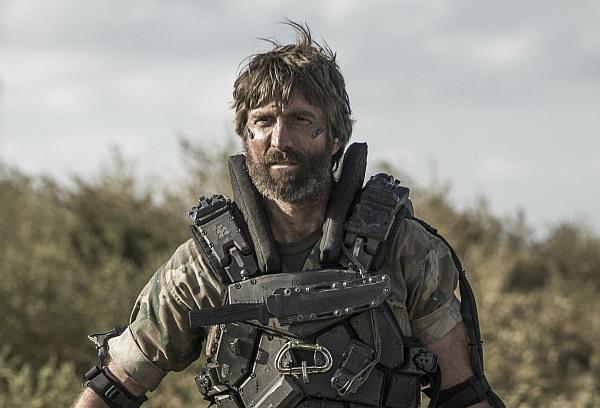 Ein bärtiger Mann in futuristisch-militärischer Kleidung - Sharlto Copley als Kruger