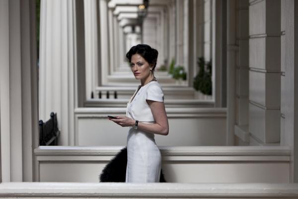 Frau in weißem Kleid vor weißen Hauseingängen.