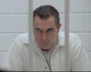 Ein Mann schaut grimmig hinter Gittern hervor.