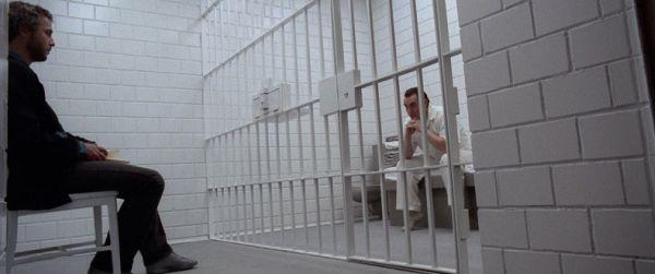 Zwei Männer sitzen sich gegenüber, der eine in einer Zelle hinter Gittern.