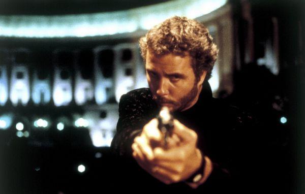 Ein bärtiger Mann zielt mit einer Pistole Richtung Betrachter