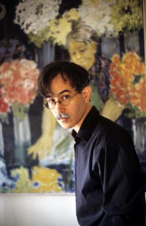 Ein neugierig blickender Mann mit Schnurrbart und Brille vor einem Gemälde mit einer Blumenfrau