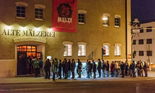Besucherschlange vor der Alten Mälzerei, circa 30 Menschen warten in der Nacht.