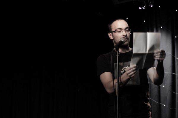 Mann mit Brille steht vor Mikro und liest einen Text von einem Blatt Papier ab.