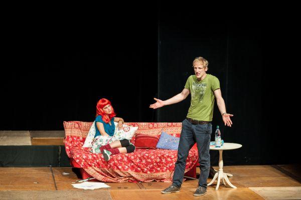 Auf einer Bühne sitzt eine Frau mit roter Perücke auf einem Sofa und schaut zu einem gestikulierendem Mann
