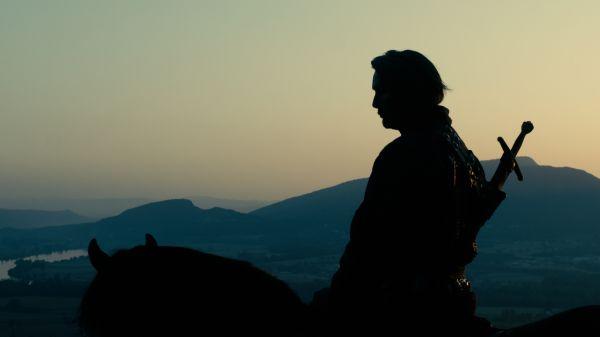 Silhouette eines Reiters vor Bergen, auf dem Rücken trägt er ein Schwert.