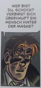 """Ein rotblonder Mann mit Nasenbluten und einem Schnitt im Gesicht. Über ihm eine Sprechblase: """"Wer bist du, Schock? Verbirgt sich überhaupt ein Mensch hinter der Maske?"""""""