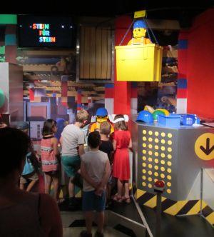 Foto aus dem Legoland Discovery Centre: Kinder stehen an einer Attraktion an, darüber schwebt in einer Gondel ein als Bauarbeiter gekleidetes Legomännchen, gebaut aus Legosteinen.