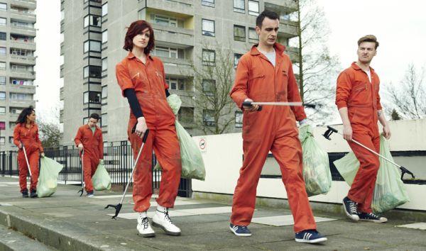 Fünf junge Leute in orangefarbenen Overalls sammeln Müll zwischen Plattenbauten ein.