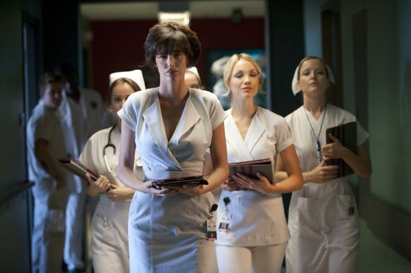 Vier Krankenschwestern gehen einen Krankenhausgang entlang, darunter Abby (Paz De La Huerta) und Danni (Katrina Bowden).