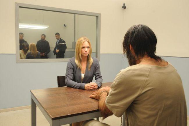 Szenenbild aus Wer - das Biest in dir: Eine Blonde Frau sitzt in einem Verhörraum einem großen, stark behaarten Mann gegenüber. Im Hintergrund ist ein Spiegel, auf dem drei uniformierte Polizisten hinter dem Mann zu sehen sind.