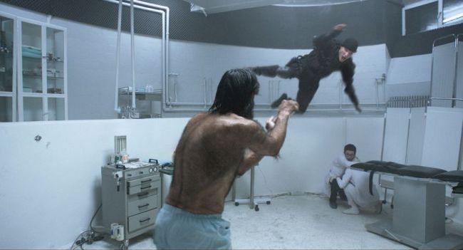 Ein haariger Mann in einem Untersuchungszimmer, Ärzte in weißen Kitteln kauern unter einer Liege, ein Mann in schwarzer Kampfmontur springt auf ihn zu.
