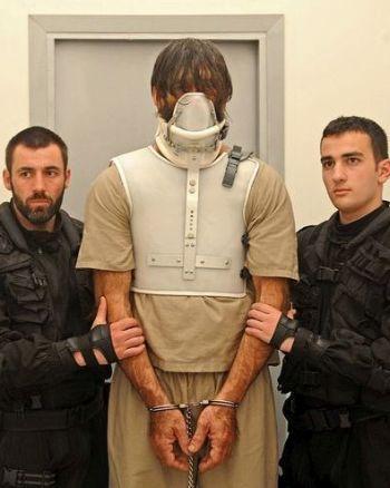 Ein großer Mann in Handschellen mit einer Maske vor dem Gesicht, den zwei deutlich kleinere Polizisten flankieren.
