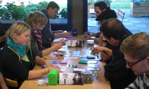 Mehrere Frauen und Männer sitzen sich an einem Tisch gegenüber, zwischen ihnen liegen viele Magic-Karten.