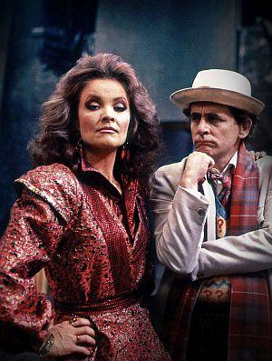 Eine Frau mit Föhnfrisur schaut selbstbewusst Richtung Kamera. Neben ihr steht ein Mann mit beigem Hut und Anzug . Er sieht grübelnd in Richtung Frau.