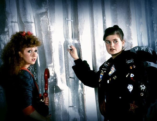 Zwei junge Frauen vor einer Eiswand. Die eine trägt einen akkuraten Blazer, die andere eine Bomberjacke voller Sticker.